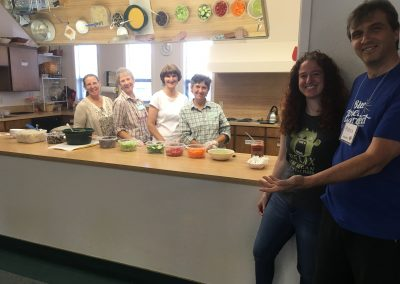 Volunteer cooks and facilitators stand ready to serve 'yum' bowls on the last day of class.